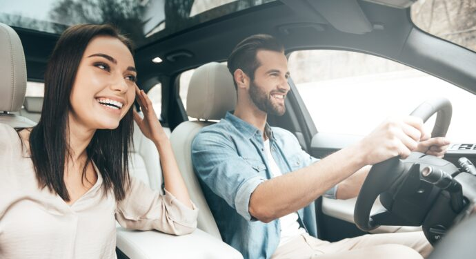 Beautiful young couple sitting on the front passenger seats and smiling while handsome man driving a car