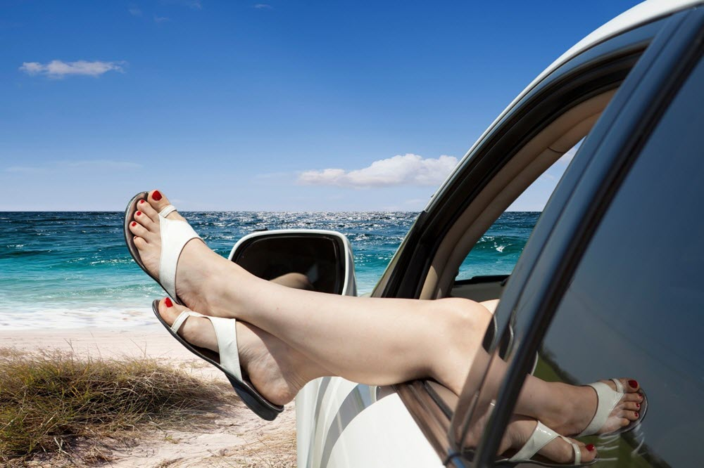 Lady with Feet out of Car Window at Beach