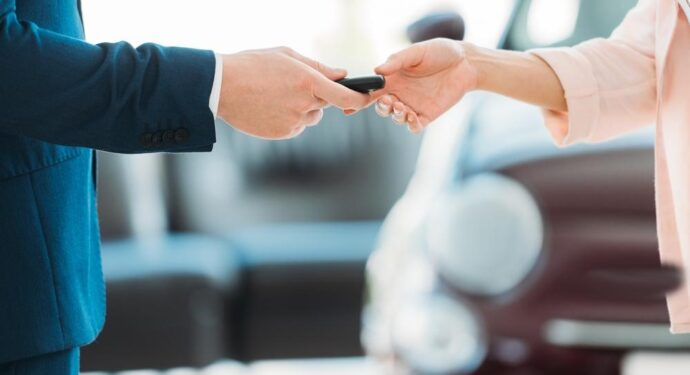 Car salesman handing keys to customer